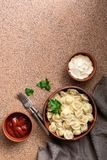 Traditional Russian food dumplings with meat served in a clay bowl with sour cream and tomato sauce. Top view, copy space.  royalty free stock photos