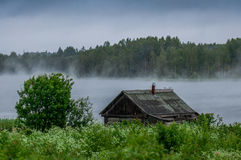 The traditional Russian log hut in poor condition on the river bank Royalty Free Stock Images