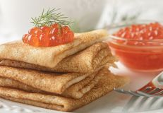 Traditional Russian pancakes blini with salmon caviar. On a white plate. Selective focus stock image