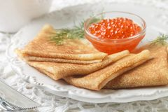 Traditional Russian pancakes blini with salmon caviar. On a white plate. Selective focus royalty free stock photo