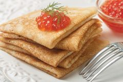 Traditional Russian pancakes blini with salmon caviar. On a white plate. Selective focus royalty free stock images