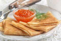 Traditional Russian pancakes blini with salmon caviar. On a white plate. Selective focus royalty free stock image