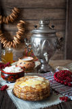 Traditional russian pancakes with cottage cheese, milk, bagels and samovar. On vintage wooden background Stock Photo