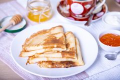 Traditional Russian pancakes with honey, sour cream and jam. royalty free stock photography