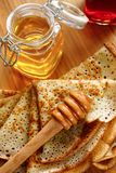 Pancakes with honey. Maslenitsa. Traditional Russian pancakes and a jar of honey Royalty Free Stock Photos