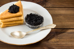 Traditional russian Pancakes on plate with black caviar. On wooden background. space for text Royalty Free Stock Photos
