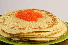 Traditional Russian pancakes with red caviar. Some pancakes with caviar on the plate and wooden board on white background Stock Images