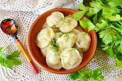 Traditional russian pelmeni with minced meat and onions filling in a brown ceramic bowl. Stock Photo