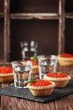 Traditional russian red caviare on the wooden table. Selective focus Stock Image