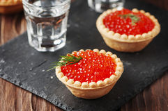 Traditional russian red caviare on the wooden table. Selective focus Royalty Free Stock Images