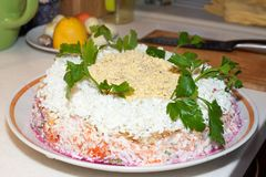 Traditional Russian salad herring under a fur coat on a large white dish decorated with greens stock images