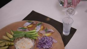Traditional russian snacks salted herring with vegetables, onion, lemon, yellow lime, bread and shots of vodka. stock video footage