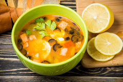 Traditional Russian soup solyanka in bowl on the table. Traditional Russian soup solyanka in green bowl on wooden table Stock Photography
