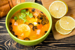 Traditional Russian soup solyanka in bowl on the table. Traditional Russian soup solyanka in green bowl on wooden table Stock Images