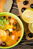Traditional Russian soup solyanka in bowl on the table. Traditional Russian soup solyanka in green bowl on wooden table Stock Image