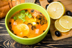 Traditional Russian soup solyanka in bowl on the table. Traditional Russian soup solyanka in green bowl on wooden table Stock Photo
