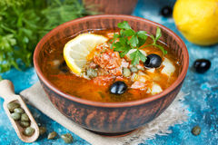 Traditional Russian soup solyanka. Soup with lemon meat olive caper tomato Royalty Free Stock Images