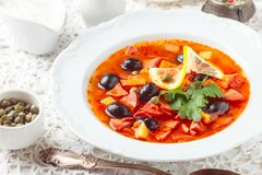 Traditional Russian soup Solyanka with meat, sausages, vegetables. Capers, pickles and olives with lemon, seasonings and spices. Served with sour cream. Rustic royalty free stock photography
