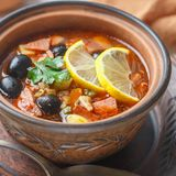 Traditional Russian soup Solyanka with meat, sausages, vegetables. Capers, pickles and olives with lemon, seasonings and spices. Served with sour cream. Rustic stock photos