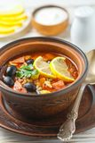 Traditional Russian soup Solyanka with meat, sausages, vegetable. S, capers, pickles and olives with lemon, seasonings and spices. Served with sour cream. Rustic stock image
