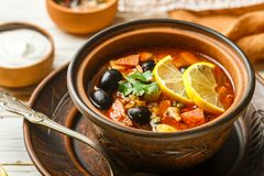 Traditional Russian soup Solyanka with meat, sausages, vegetable. S, capers, pickles and olives with lemon, seasonings and spices. Served with sour cream. Rustic stock photography