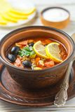 Traditional Russian soup Solyanka with meat, sausages, vegetable. S, capers, pickles and olives with lemon, seasonings and spices. Served with sour cream. Rustic stock images