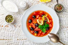Traditional Russian soup Solyanka with meat, sausages, vegetables. Capers, pickles and olives with lemon, seasonings and spices. Served with sour cream. Rustic royalty free stock images