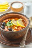 Traditional Russian soup Solyanka with meat, sausages, vegetables. Capers, pickles and olives with lemon, seasonings and spices. Served with sour cream. Rustic royalty free stock photos