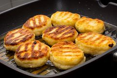 Traditional Russian sweet syrniki cottage cheese pancakes fried in the frying pan Stock Photos