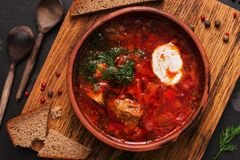Traditional Russian Ukrainian borscht red soup with rye bread on a dark background. Borsch with meat, sour cream and dill. royalty free stock photos
