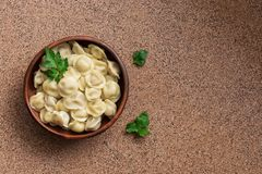 Traditional Russian and Ukrainian food pelmeni meat Dumplings on a brown stone background. Top view, copy space stock photography