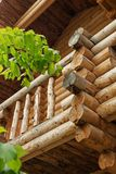Traditional Russian wooden construction, the corner of the house with logs, round bars on the wall of the house, the ends of fell Stock Photography