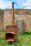 Traditional rusty metal wood oven in backyard in a sunny summer day. Royalty Free Stock Photo