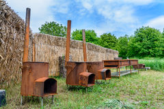 Traditional rusty metal wood oven in backyard in a sunny summer day. Royalty Free Stock Image
