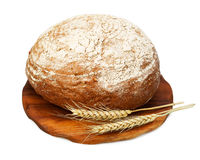 Traditional rye bread and wheat on a wooden board Stock Photos