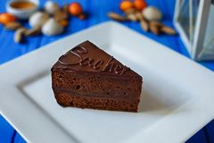 Traditional sacher cake sliced on white squared plate stock photography