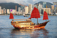 Traditional Sail junk ship in modern Hong Kong. Sunset view of a traditional, junk ship with wind sails shot against modern cityscape of Hong Kong island Royalty Free Stock Images