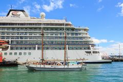 A traditional sailing ship alongside a cruise liner. The `Ted Ashby`, a traditionally built sailing scow, looks tiny alongside the hull of the `Viking Orion`, a stock photography