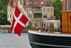 Traditional sailing ship with large Danish national flag hanging from the stern in the harbor of Sonderborg, Denmark. With picturesque timber-framed residential Royalty Free Stock Photo