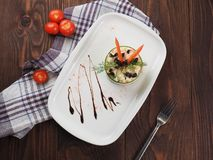 Traditional salad with cooked vegetables with mayonnaise. Vegetable salad with mayonnaise on a plate, rustic background. Top view royalty free stock photo