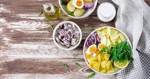 Traditional salad of salted herring fillet, eggs, fresh apples, red onion and potatoes. Kosher food. Scandinavian cuisine. Top view. Flat lay royalty free stock photo