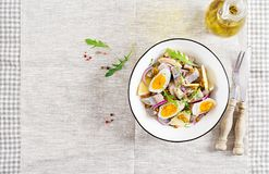 Traditional salad of salted herring fillet, fresh apples, red onion and eggs. Kosher food. Scandinavian cuisine. Top view. Flat lay royalty free stock images