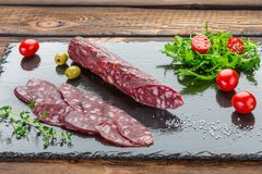 Traditional salami sliced on dark stone board. Top view with copy space on wooden background. royalty free stock image
