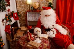 Traditional Santa Claus checks his list in a notebook stock image