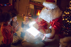 Traditional Santa Claus with children and magical present. Open gift box with magical effect Stock Images