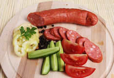 Traditional sausages on a platter. With fresh tomatoes, capsicum, and cucumbers Royalty Free Stock Images
