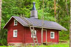 Traditional Scandinavian red wooden house in forest. Traditional Scandinavian red wooden house on green forest background. Kotka, Finland Royalty Free Stock Images
