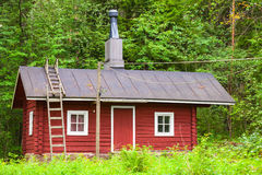 Traditional Scandinavian red wooden house. Over green forest background. Kotka, Finland Royalty Free Stock Photos