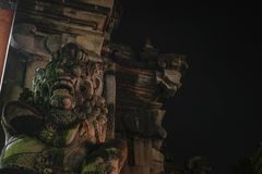 Traditional scary looking Bali island stone sculpture at night royalty free stock photography