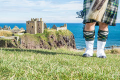 Traditional scottish bagpiper in full dress code at Dunnottar Castle Stock Image